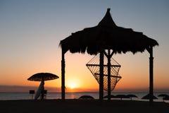 Hamac à la plage pendant le coucher du soleil Images stock
