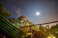 Hamac la nuit avec le fullmoon et les étoiles devant une montagne dans la ville de Phong Nha en parc national de Phong Photos stock