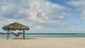 Hamaca, choza, y playa Foto de archivo libre de regalías