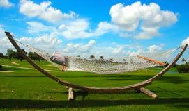Hamaca de madera en un día asoleado y un cielo azul brillante imagen de archivo libre de regalías