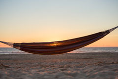 Hamaca en puesta del sol en la playa Fotos de archivo