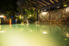 Hamacas and swimming-pool. A few hamacas to relax over a swimming-pool Stock Photos