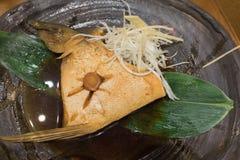 Hamachi lagade mat i sås på den svarta keramiska plattan Arkivfoton