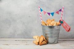 Hamantaschen ciastka lub hamans ucho w wiadrze nad nieociosanym tłem dla Żydowskiego wakacyjnego Purim obraz royalty free