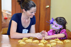 Hamantaschen cookie cooking in Purim Holiday. Jewish Mother and her child (daughter girl age 5) in costume preparing and cooking togather home made Hamantaschen Royalty Free Stock Images