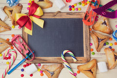 Hamantaschen cookies and chalkboard on wooden white table. View from above Royalty Free Stock Photo