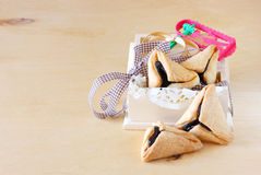 Hamantaschen cookies or hamans ears and Noisemaker for Purim celebration in wooden box. Pic stock photo