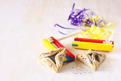 Hamantaschen cookies or hamans ears for Purim celebration and noisemaker. Over textured wooden board stock photo