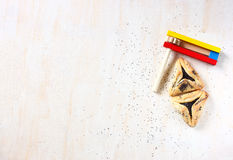 Hamantaschen cookies or hamans ears for Purim celebration and noisemaker Royalty Free Stock Photography