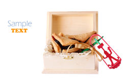 Hamantaschen cookies or hamans ears for Purim celebration in wooden box and Noisemaker isolated Royalty Free Stock Image