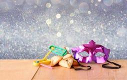 Hamantaschen kakor eller hamansöron, noisemakeren och maskeringen för Purim beröm (judisk ferie) och blänker bakgrund Royaltyfri Bild