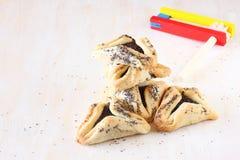 Hamantaschenkoekjes of hamans oren voor Purim-viering en noisemaker Royalty-vrije Stock Foto's