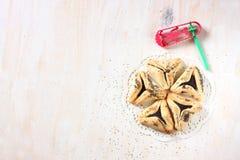 Hamantaschenkoekjes of hamans oren voor Purim-viering en noisemaker Stock Foto