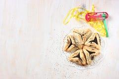 Hamantaschenkoekjes of hamans oren voor Purim-viering en noisemaker Stock Afbeeldingen