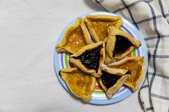 Hamantash Purim blueberry and apricot jam cookies on colored plate with a plaid blue rag and a white sheet background stock photo