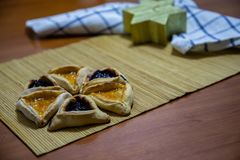 Hamantash Purim blueberry and apricot jam cookies with wooden table background and David star shape candle stock photography