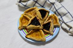 Hamantash Purim czarna jagoda i morelowi d?em?w ciastka na barwionym talerzu z szkockiej kraty b??kita ?achmanem i bia?ym szkotow obraz stock