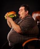 Hamberger mangiatore di uomini grasso degli alimenti a rapida preparazione Prima colazione per la persona di peso eccessivo immagine stock libera da diritti
