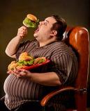 Hamberger mangiatore di uomini grasso degli alimenti a rapida preparazione Prima colazione per la persona di peso eccessivo fotografia stock