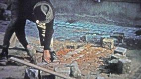 HAMBOURG, ALLEMAGNE - 1966 : Équipez réparer la route de pavé rond avec des techniques de mère patrie banque de vidéos