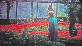 HAMBOURG, ALLEMAGNE - 1966 : Femmes marchant par le jardin conservateur de fleur rouge au plus fort de la fleur clips vidéos