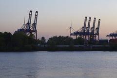 Hamburg - behållarelastningsbryggakranar i aftonen Royaltyfri Fotografi