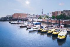 Hamburg cityscape. Excursion boats in Hamburg harbor near Baumwall station with steeple of Sankt Michaelis church in background Stock Photos