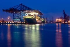 Hamburg container port, long exposure shot by night. Panoramic view of the industrual container port in Hamburg during dusk and night royalty free stock images