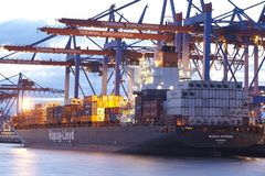 Hamburg - Container vessel at terminal in the evening Stock Photos