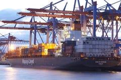Hamburg - Containerschip bij terminal in de avond Stock Foto's