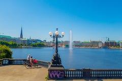 HAMBURG, DEUTSCHLAND - 8. JUNI 2015: Zwei Radfahrer stoppen, um das Spritzenwasser mitten in dem Innensee herein zu sehen Lizenzfreie Stockbilder