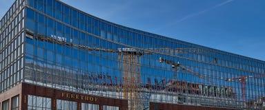 HAMBURG, DEUTSCHLAND - 26. MÄRZ 2016: Das neue Bürogebäude Fleethof in Hamburg reflektiert einen großen Kran und den blauen Himme Stockfotos