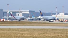HAMBURG, DEUTSCHLAND - 7. März 2014: Werden Emirat- und Lufthansa-A380 Flugzeug vor der Airbus-Anlage herein gepasst Stockbilder