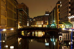 Hamburg downtown at night. Night scene of a channel in Hamburg with buildings on either side with a bridge over the water and parts of a lock in the front stock image