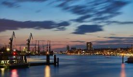 HAMBURG, DUITSLAND - MAART 27, 2016: Het toneelpanorama van wharfs, de rivier Elbe, en de verlichte huizen bij de rivier wandelen royalty-vrije stock foto