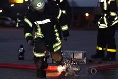 Hamburg, Germany - April 18, 2013: HDR - firefighter in action with a fire hose in the evening Stock Photos