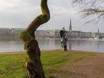 View at tree and sculpture named Windsbraut, whirlwind and Binnenalster in Hamburg, Germany. stock photography