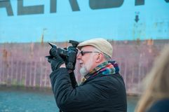 Photographer with a DSLR camera taking a photo. Hamburg Germany - December 16. 2017: Photographer with a DSLR camera taking a photo Royalty Free Stock Photos