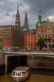HAMBURG, GERMANY - JULY 18, 2015: ferry on the canal of Historic Speicherstadt houses and bridges at evening with amaising skyview Royalty Free Stock Image