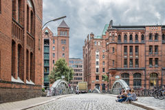 Hamburg , Germany - July 14, 2017: Young folks sitting in the streets of the famous Speicherstadt Stock Images
