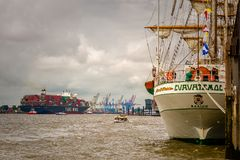 Hamburg, Germany, June 06, 2016: Mexican training ship, Cuauhtemoc, laying at anchor in port of Hamburg and big vessel in back. Royalty Free Stock Image