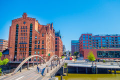 HAMBURG, GERMANY - JUNE 08, 2015: Pederestian bridge over a river, at the end of the bridge emblematic and historic. Contruction on bricks, sunny day Royalty Free Stock Photos