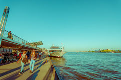 HAMBURG, GERMANY - JUNE 08, 2015: River pier on Hamburg, people can walk and eat at the side of the river. Big boat and. Girls walking on a sunny day Royalty Free Stock Images