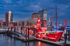 HAMBURG, GERMANY - MARCH 27, 2016: The red fire patrol boat in the marina of Hamburg with its restaurant waits for stock photo
