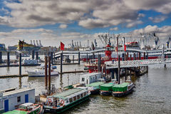 HAMBURG, GERMANY - MARCH 26, 2016: Sightseeing boats and other vessels line up at the famous Landungsbruecken of St. Pauli at the River Elbe stock photo