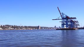 HAMBURG, GERMANY - MARCH 8th, 2014: View on the Burchardkai of the Hamburg harbor. Container ship TABEA is unloaded and. Loaded during a clear blue sky day Royalty Free Stock Photo