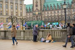 Hamburg, Germany, 22 November 2017. The citizen communicates with a homeless person sitting on the ground in front of the city hal royalty free stock photo