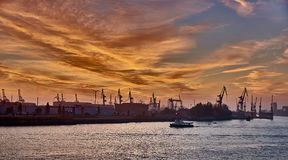 HAMBURG GERMANY - NOVEMBER 01 2015: A lonely sightseeing ship passes along the silhouette of the famous docks of the Stock Photography