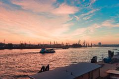 HAMBURG, GERMANY - NOVEMBER 01, 2015: One of the last sightseeing boats on river Elbe passes a scenic sundown over the royalty free stock image
