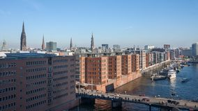 HAMBURG, GERMANY. View of new office buildings in Speicherstadt. Beautiful view of the red office buildings, the bridge and the steeples of churches on a sunny stock photo